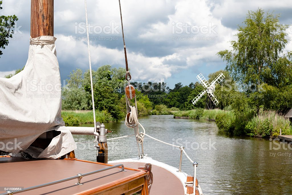 sailing boat and windmill on river on Norfolk Broads England stock photo