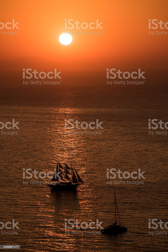 Sailing boat at sunset in Santorini stock photo