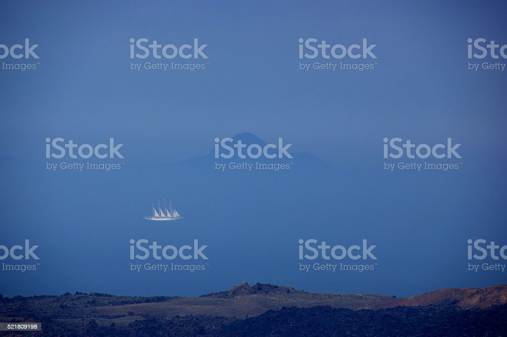 Sailing boat between two islands stock photo