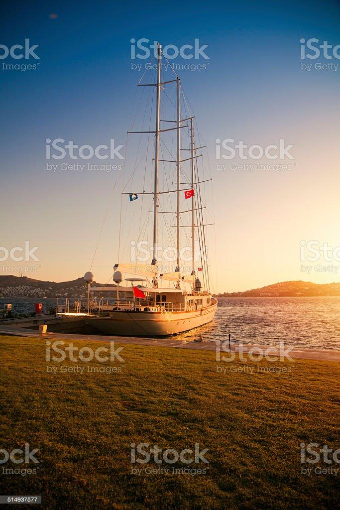 Sailing boat in marina at sunset stock photo