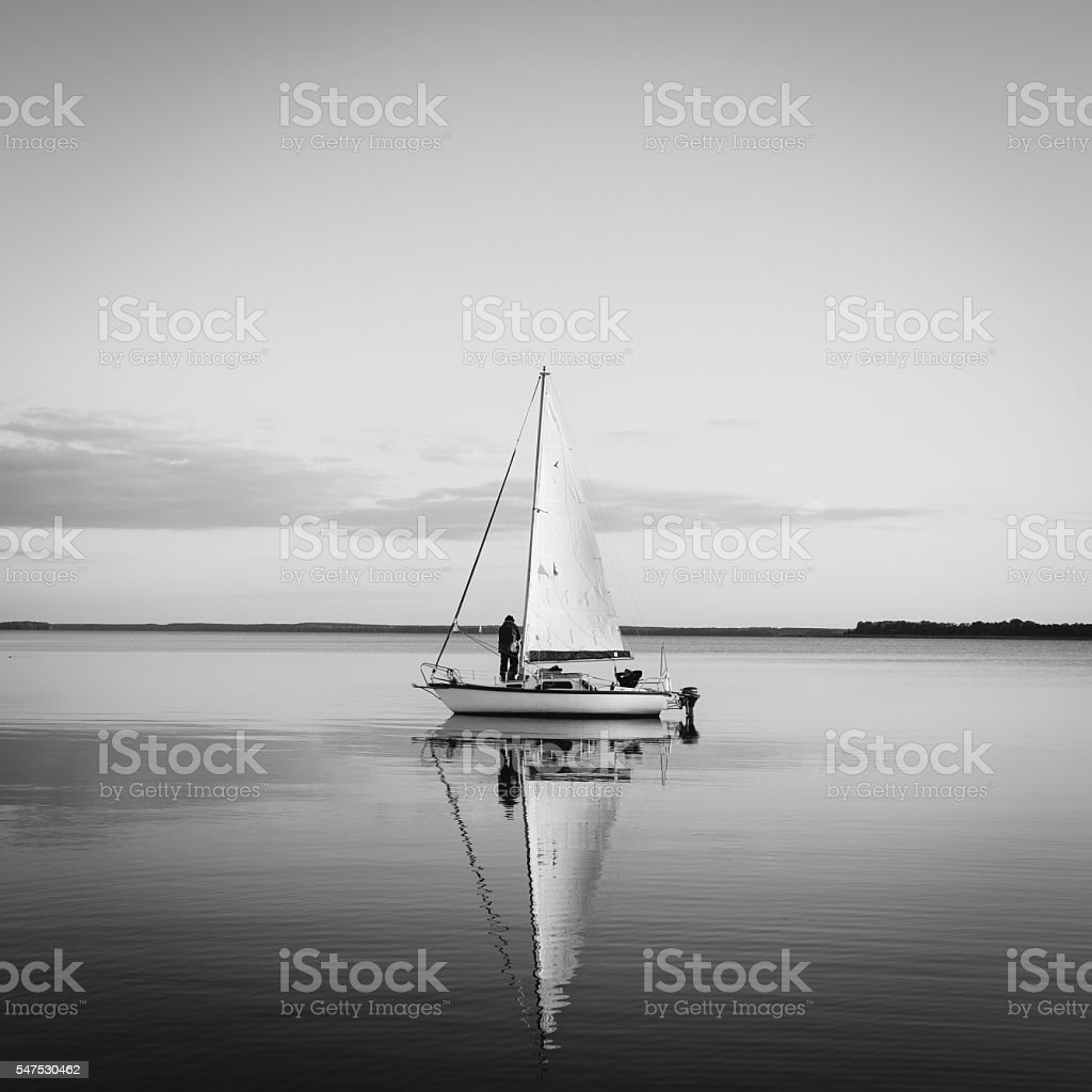 Sailing boat on a calm lake with reflection stock photo