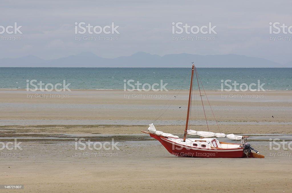 Sailing boat on desolate beach stock photo