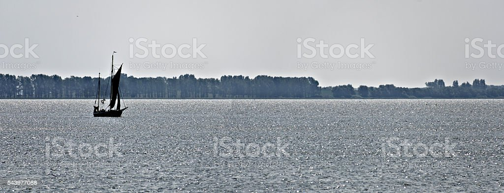 sailing boat on glittering water stock photo
