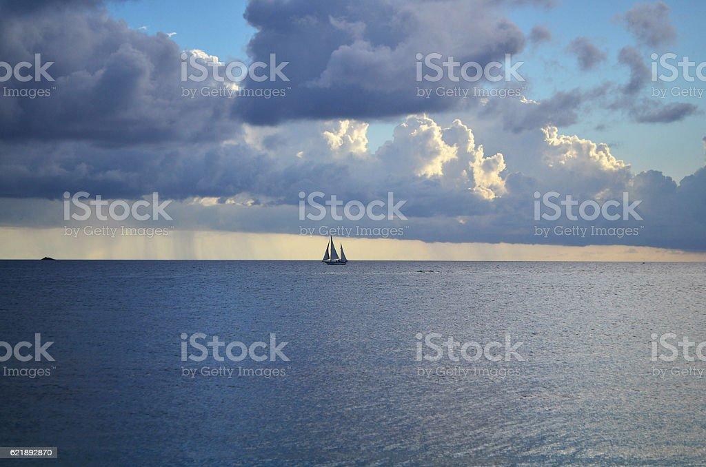 sailing boat on serene otherworldly calm sea stock photo