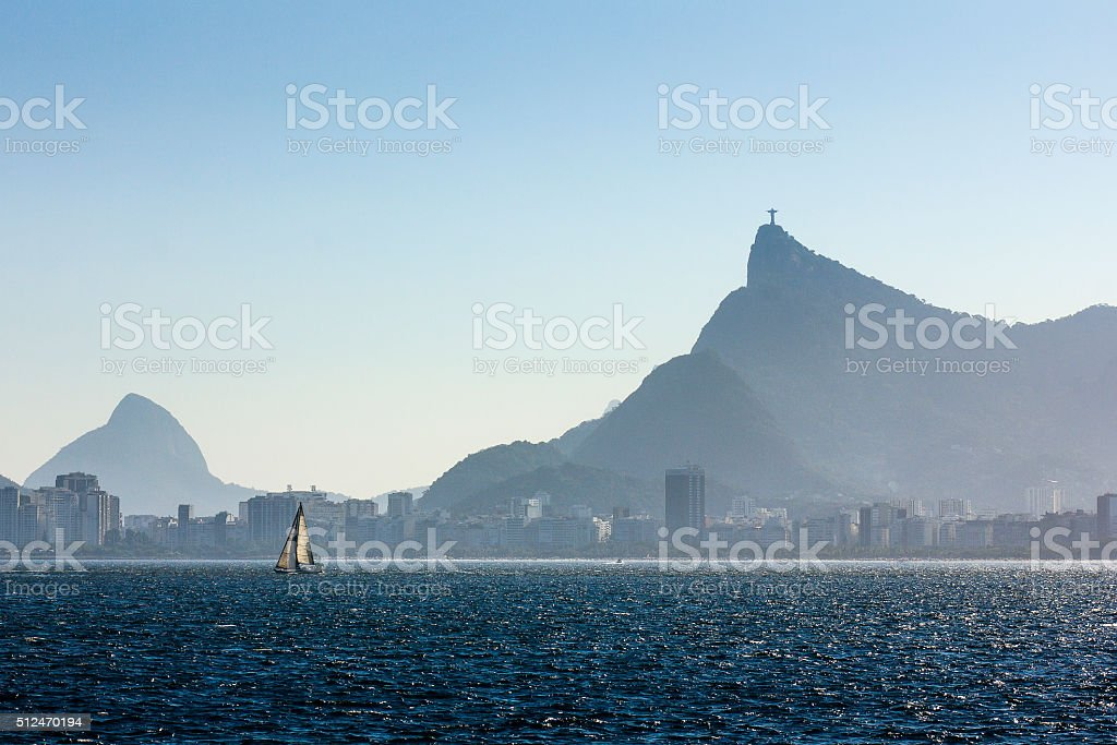 Sailing Boat Sailing in Guanabara Bay with Christ the Redeemer stock photo