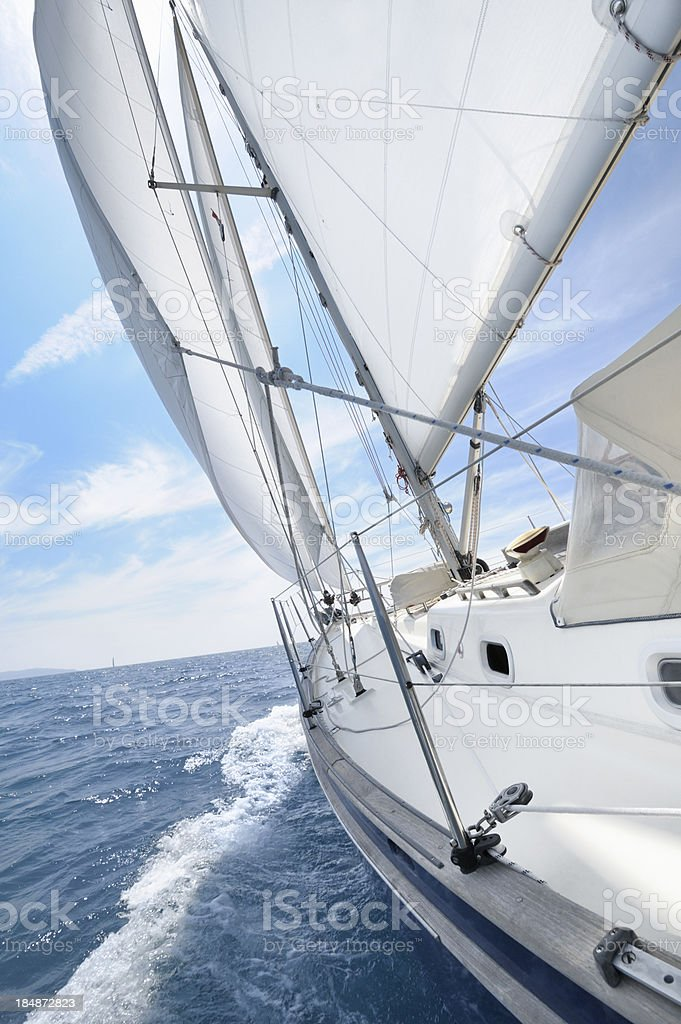 Sailing boat under sails going towars horizon royalty-free stock photo