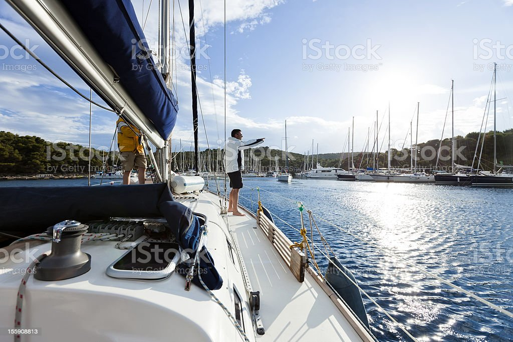 Sailing boat with crew approaching marine royalty-free stock photo