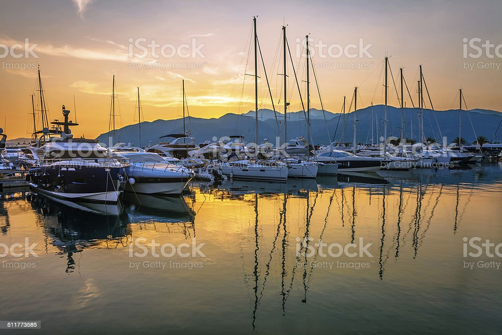 Sailing boats in marina at sunset. stock photo