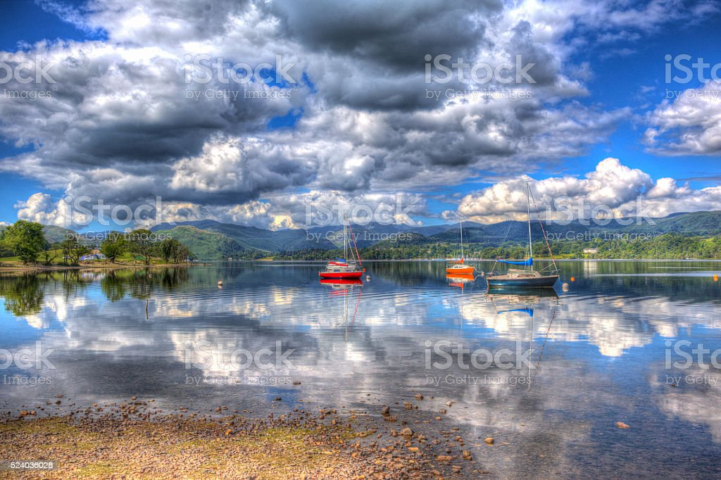 Sailing boats on calm lake with hills and clouds hdr stock photo