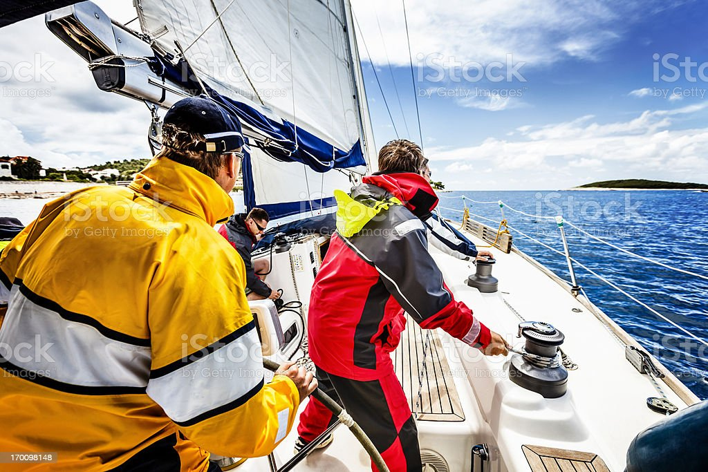 Sailing crew beating to windward on sailboat stock photo