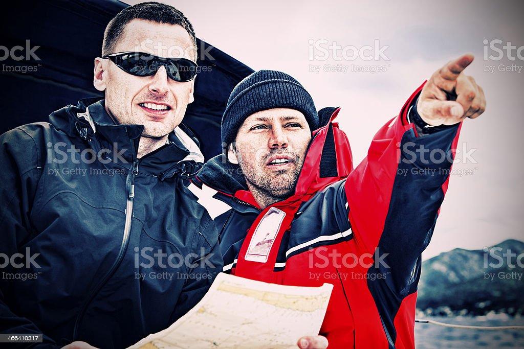 Sailing crew on sailboat checking route stock photo