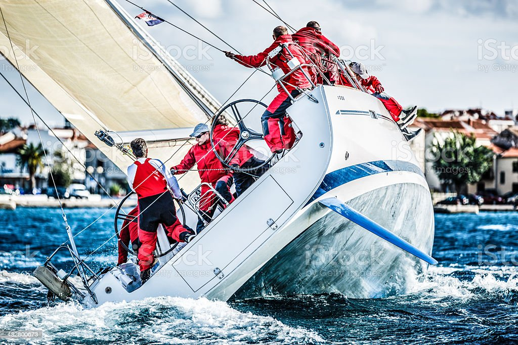 Sailing crew on sailboat during regatta stock photo