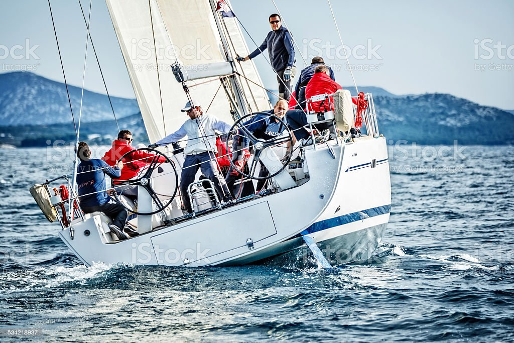 Sailing crew on sailboat during regatta stock photo