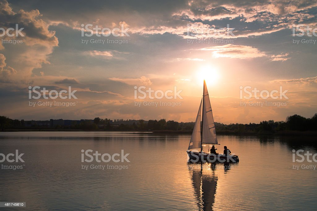 Sailing in sunset stock photo