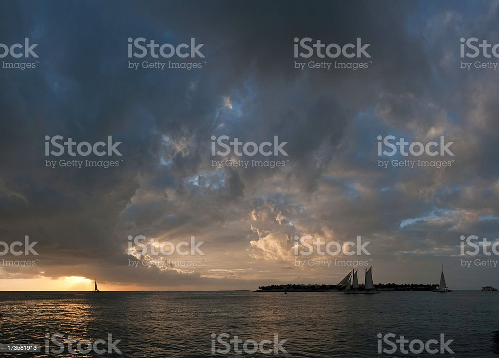 Sailing into tropical island sunset stock photo