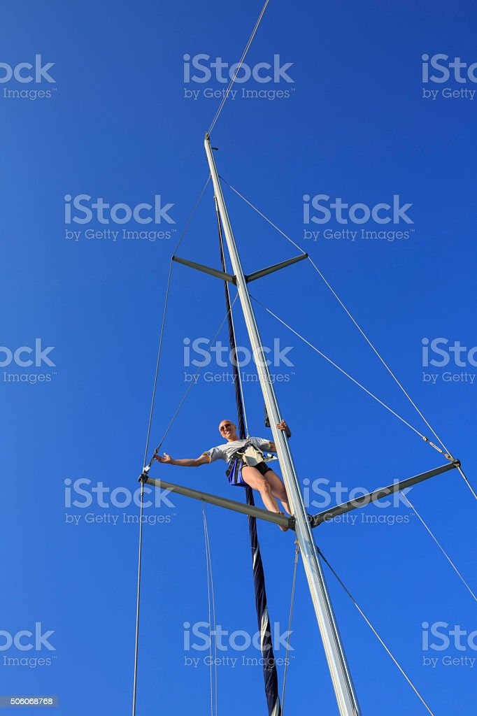 Sailing Man get up on the mast and do repairations stock photo