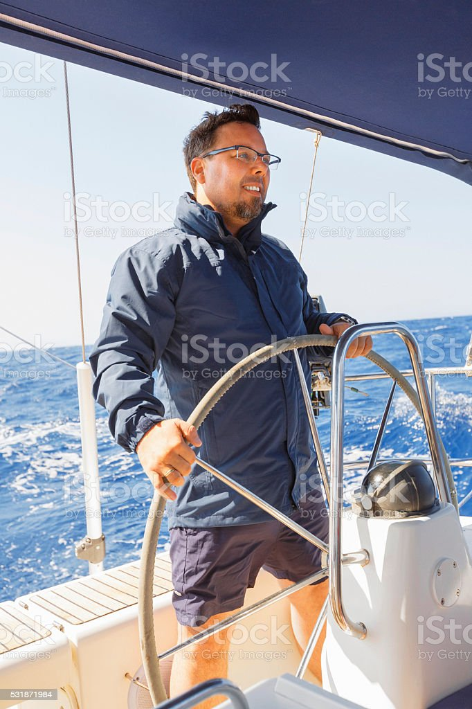 Sailing  Men skipper on a rudder of a sailboat stock photo
