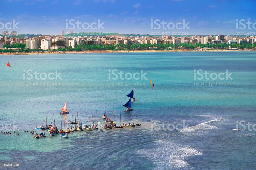 Sailing rafts and sunbathers in Maceio stock photo