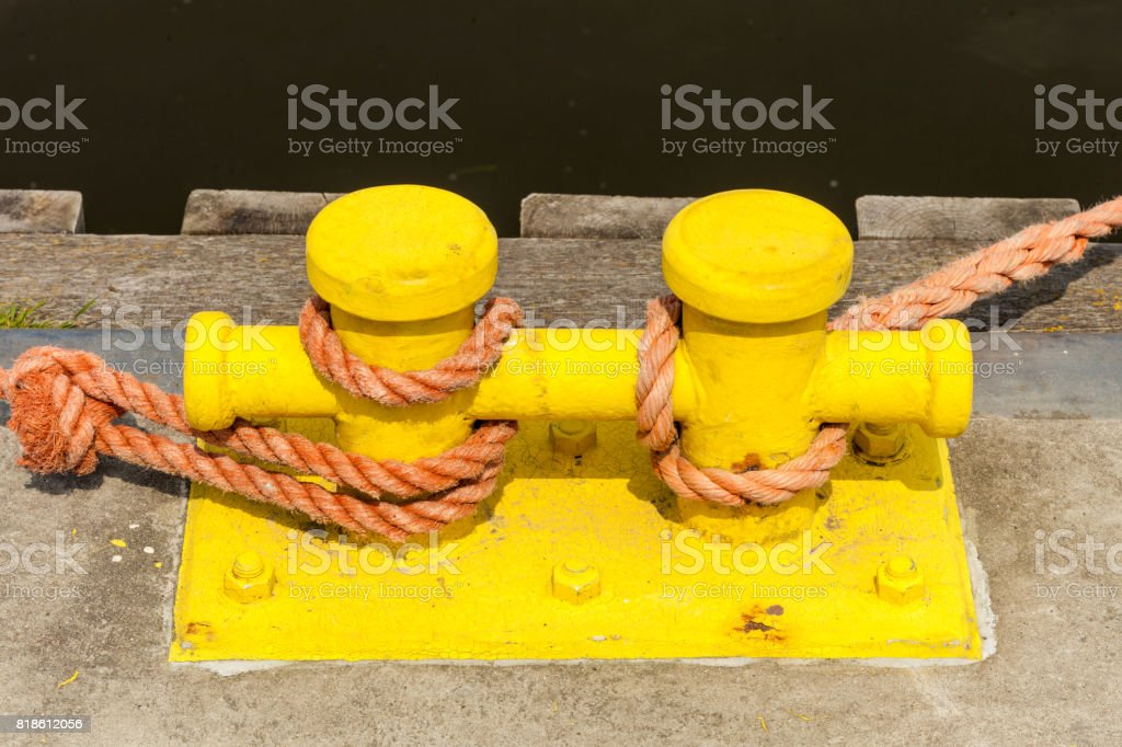 Sailing ropes tied around pins in sunlight stock photo