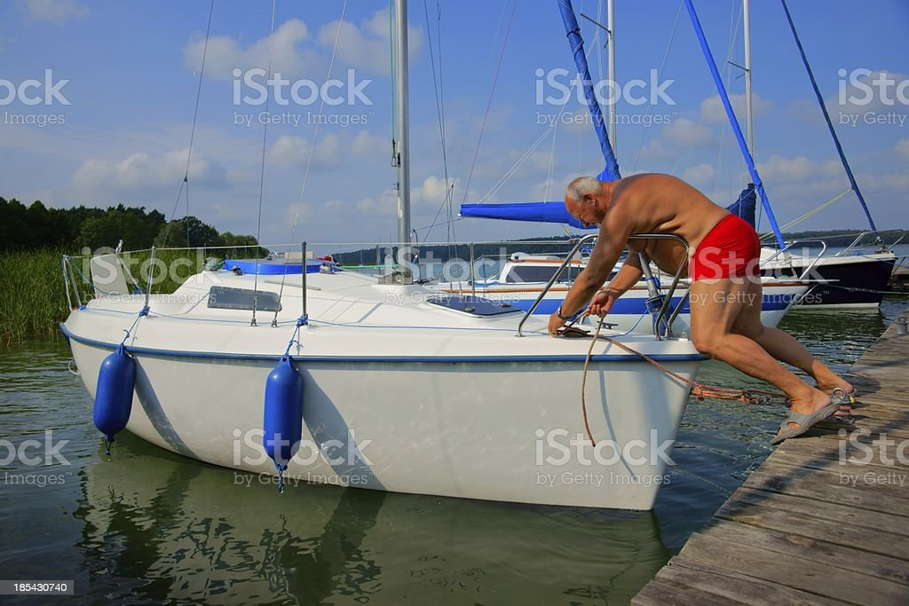 Sailing. Senior man sailboat moored to the pier royalty-free stock photo