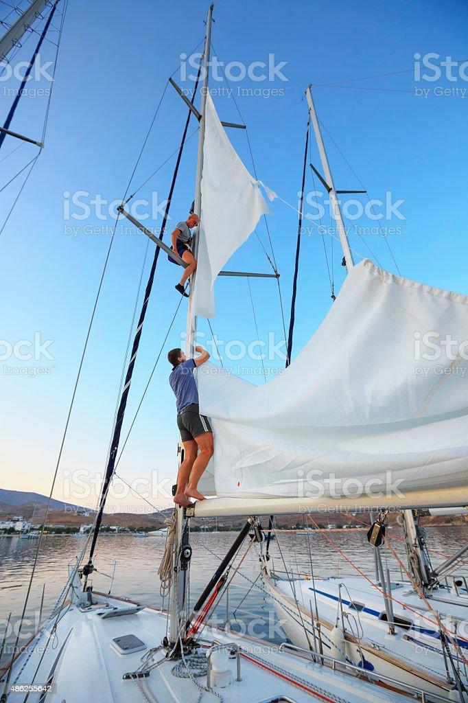 Sailing  Team sailors repaired torn sail stock photo