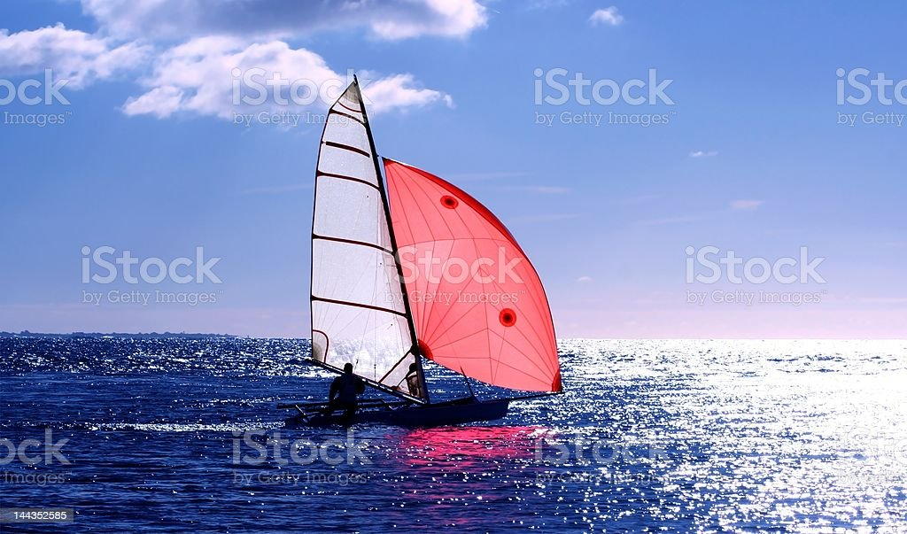 Red Sail, dinghy sailing into the sun on a blue sea : Istockphoto