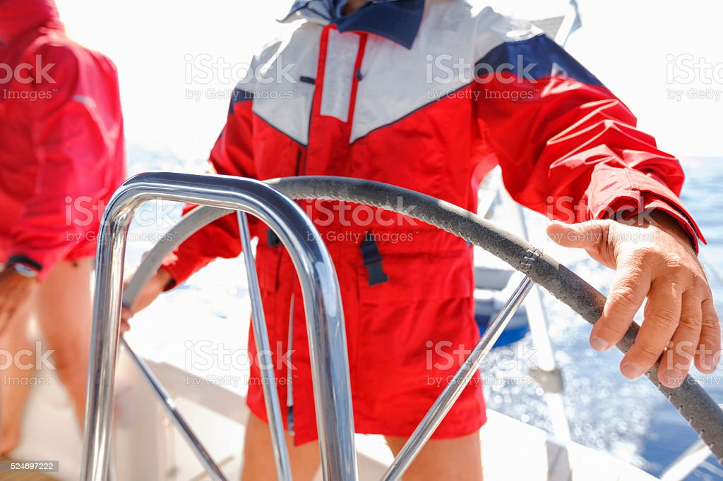 Sailing  Two men skipper on a rudder of a sailboat stock photo