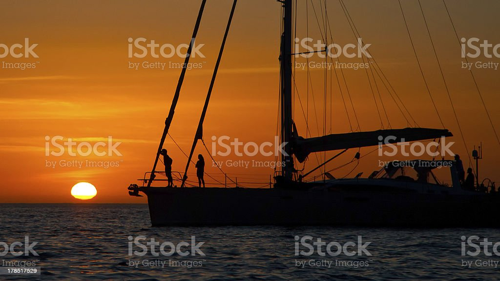 sailing yacht against a setting sun royalty-free stock photo