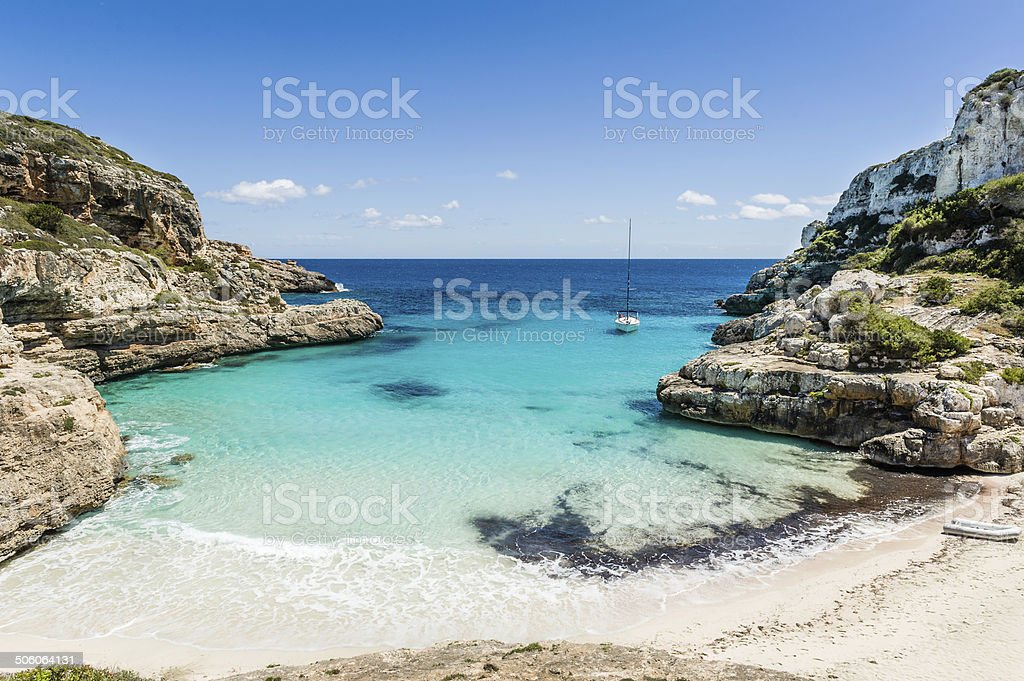 Sailing yacht in wild bay and lonely beach stock photo