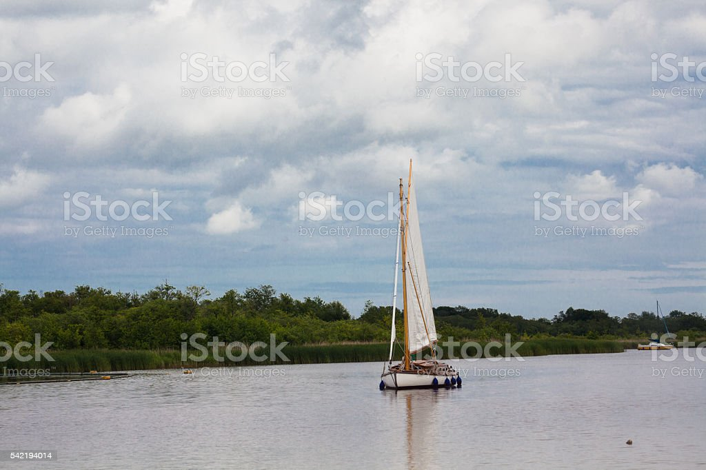 sailing yacht on calm Norfolk Broads England with threatening sky stock photo
