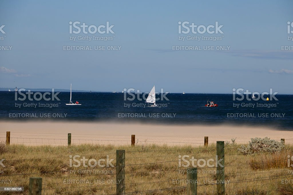 Sailing Yachts Close to Shore with Wind Blowing Sand stock photo
