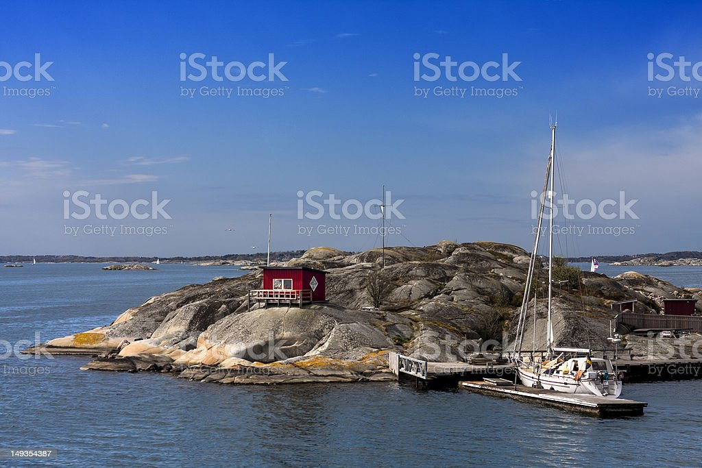 Sailingboat docked at small island with a red cottage stock photo