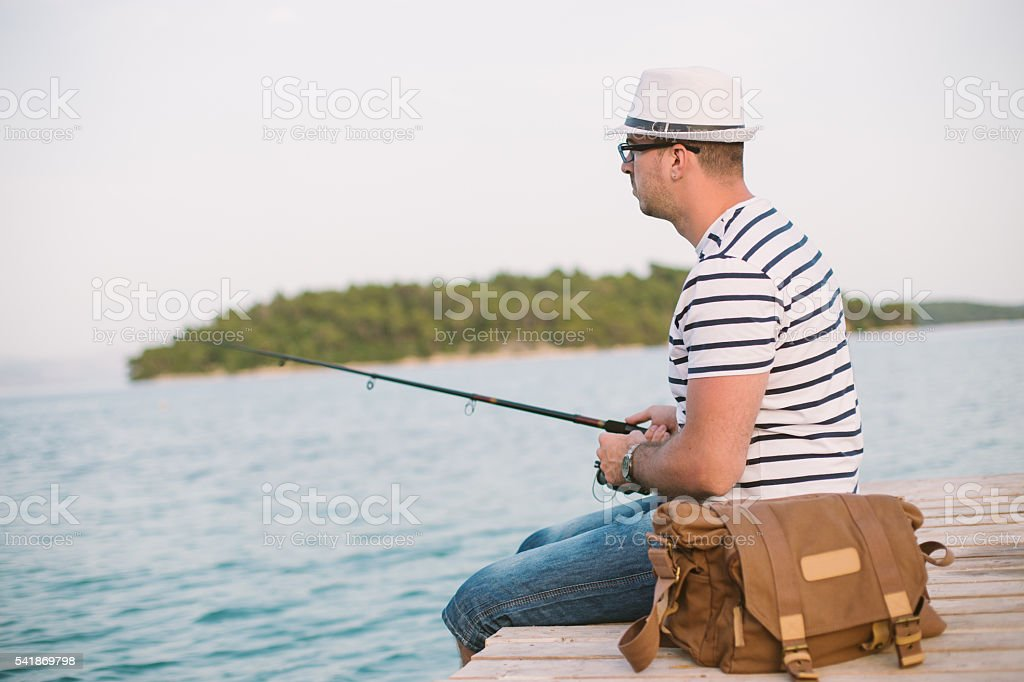 Sailor fishing on a dock stock photo