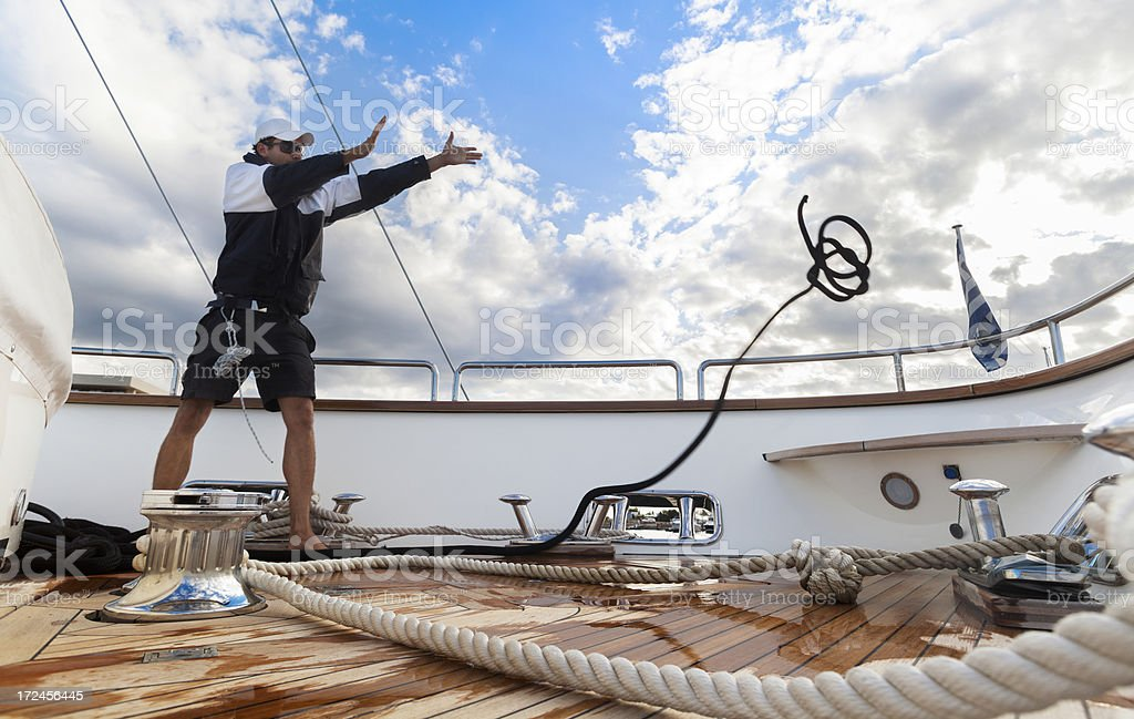 Sailor on the yacht throwing ropes. Sport. Summer. royalty-free stock photo