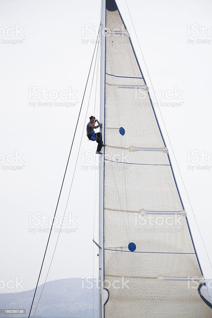 Sailor repairing on sail stock photo