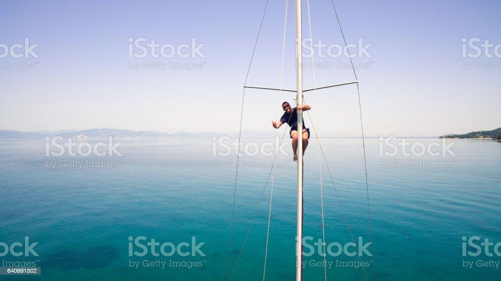 Sailor saluting from mast of sailboat stock photo