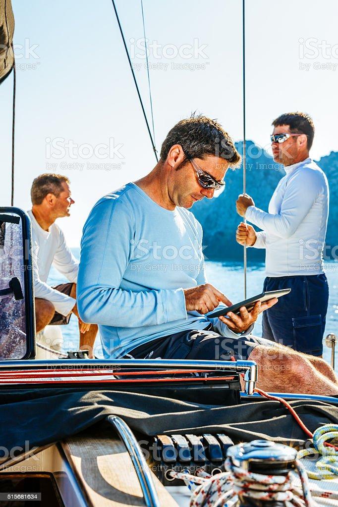 Sailor using digital tablet on sailboat stock photo