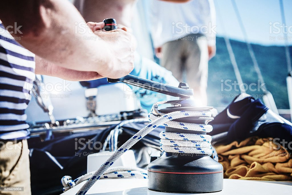 Sailor winding rope of foresail with rotating handle on winch stock photo