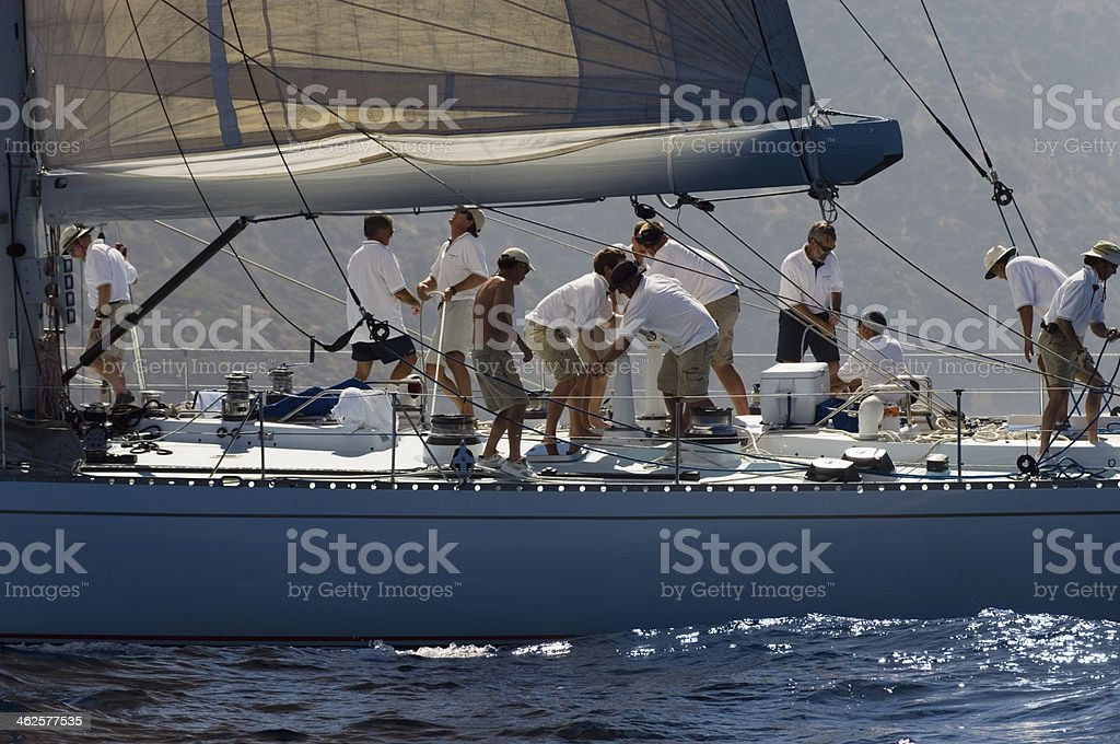 Sailors working on a sailboat during race stock photo