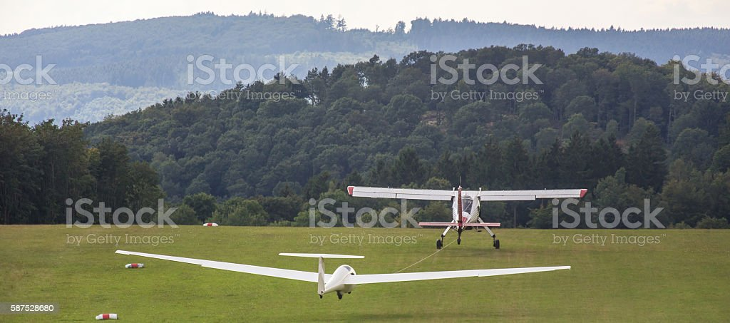 sailplane and a  towing aircraft starting on an airfield stock photo