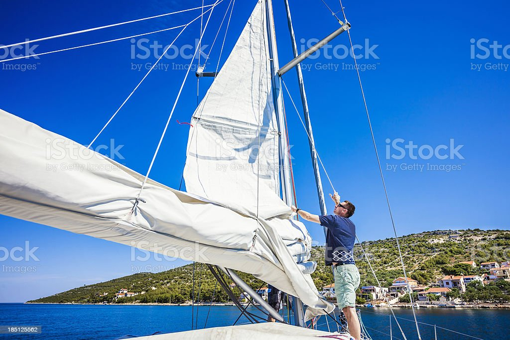 Sails up, sailor is controlling hoisting the mainsail royalty-free stock photo