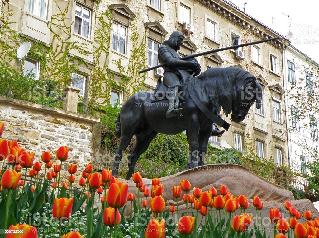 Saint George Killing Dragon, Statue amongst Blooming Vibrant Color Tulips stock photo