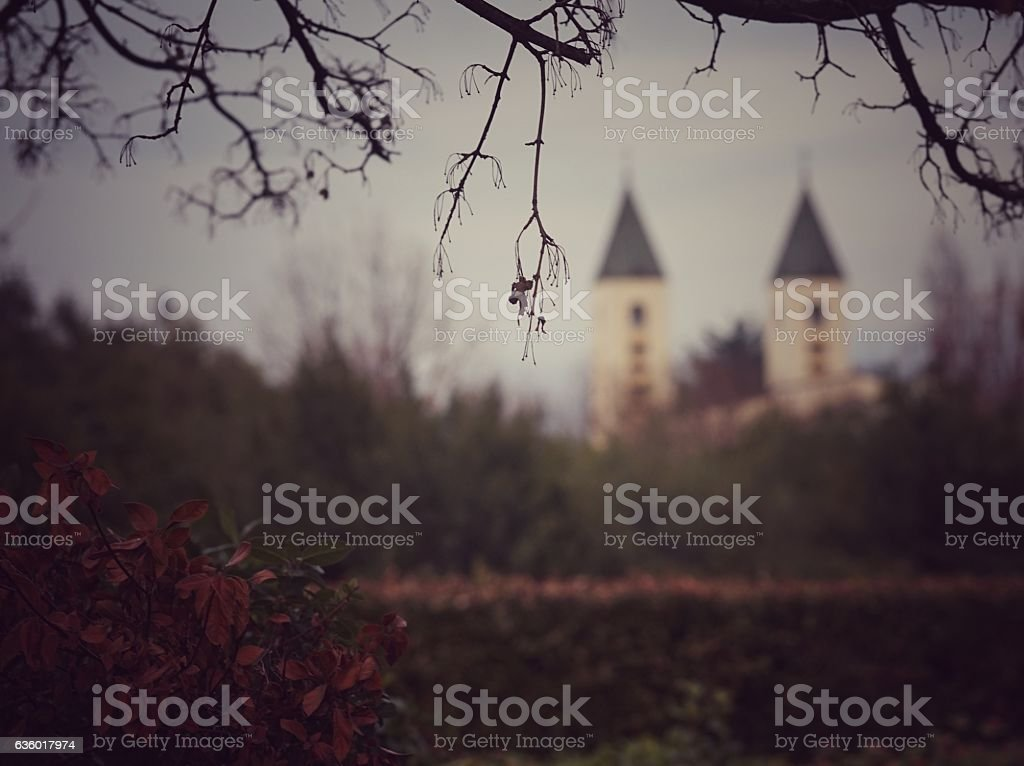 Saint James Church Steeples Through Trees and Garden, Medjugorje, Bosnia stock photo