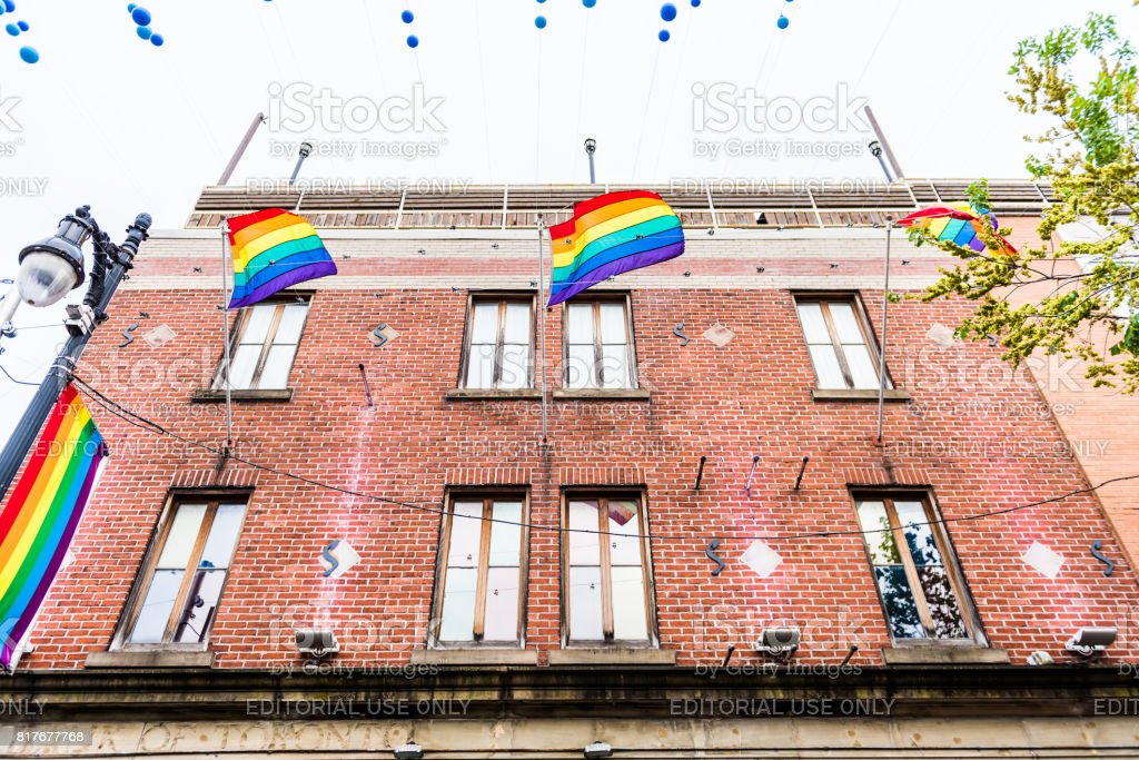 Sainte Catherine street in Montreal's Gay Village in Quebec region with hanging decorations and rainbow flags stock photo