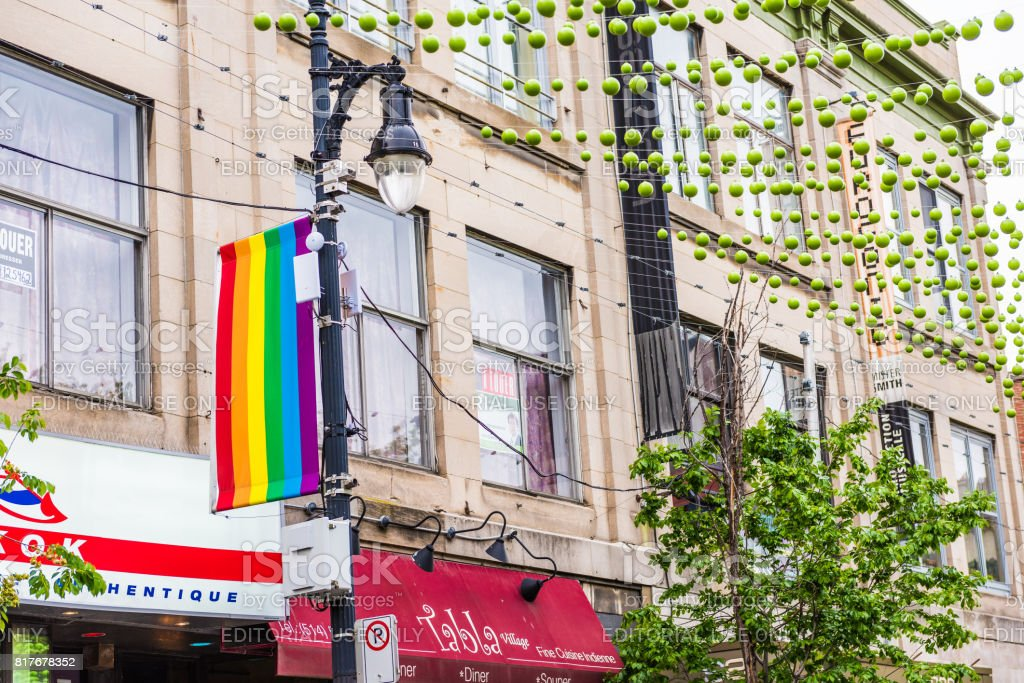 Sainte Catherine street in Montreal's Gay Village in Quebec region with green hanging decorations and lgbt flag stock photo