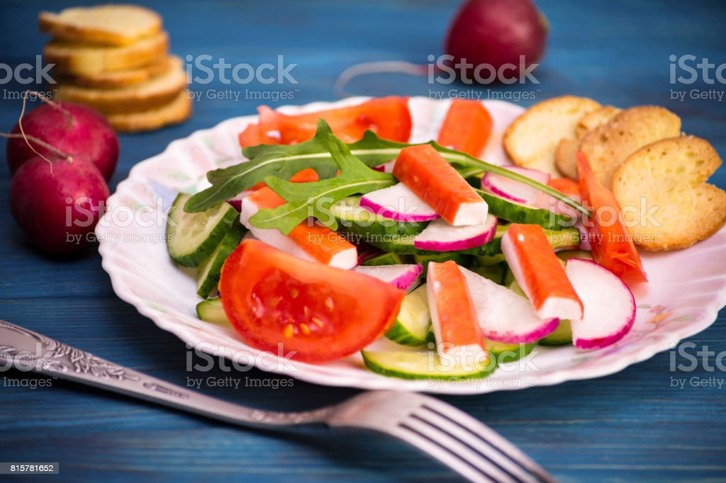 Salad from vegetables and crab sticks stock photo