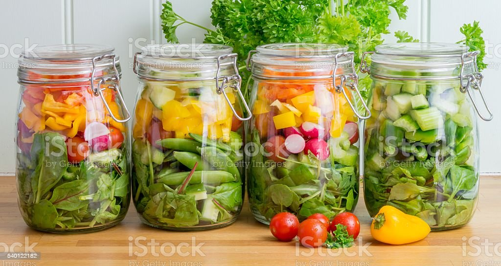 Salad in glass storage jars. Four in a line. stock photo