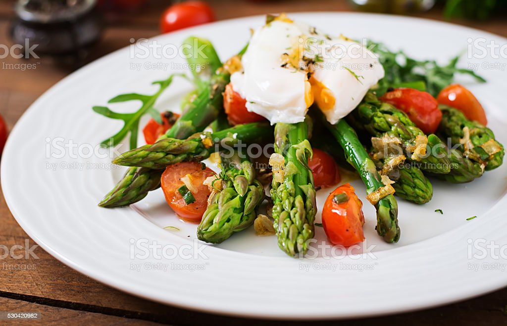 Salad of asparagus, tomatoes and poached egg stock photo