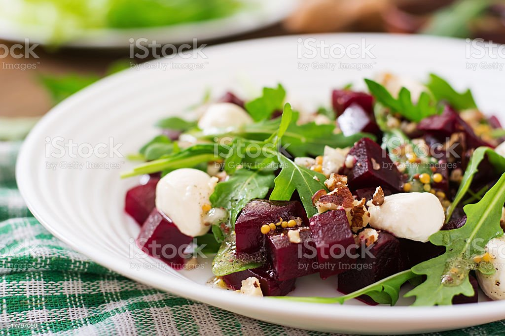 Salad of baked beets, arugula, cheese and nuts stock photo