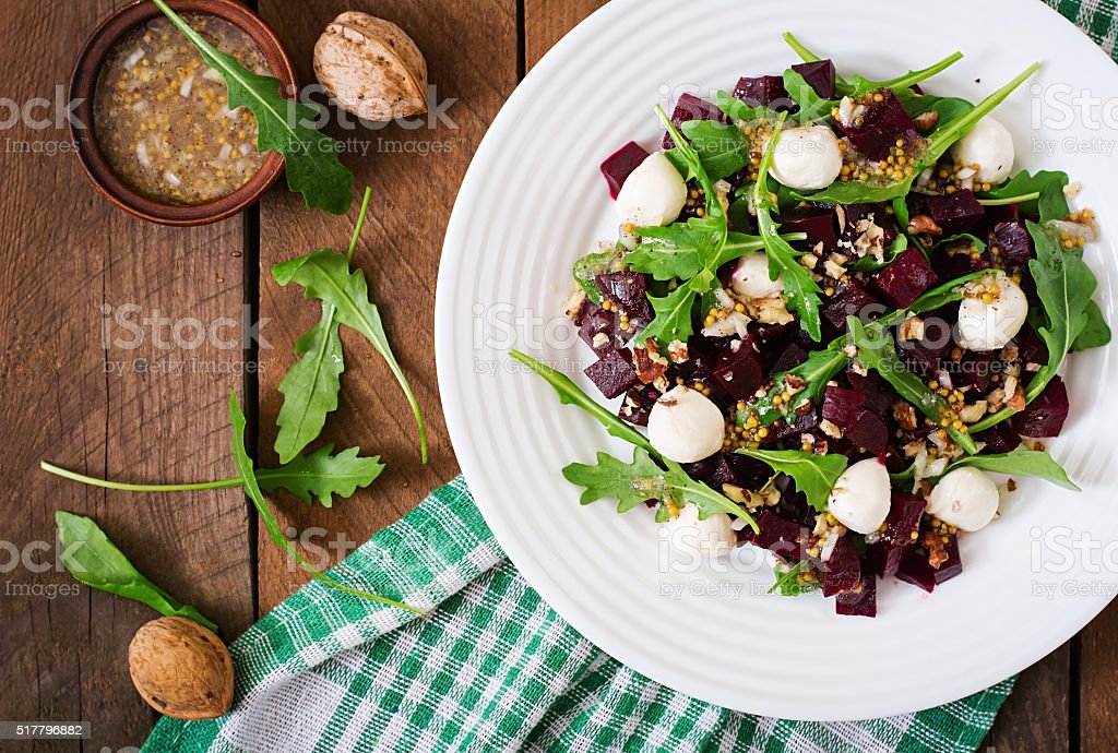Salad of baked beets, arugula, cheese and nuts. Top view stock photo